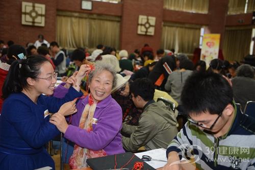清华大学志愿者和老人一起完成美丽红火的中国结_副本